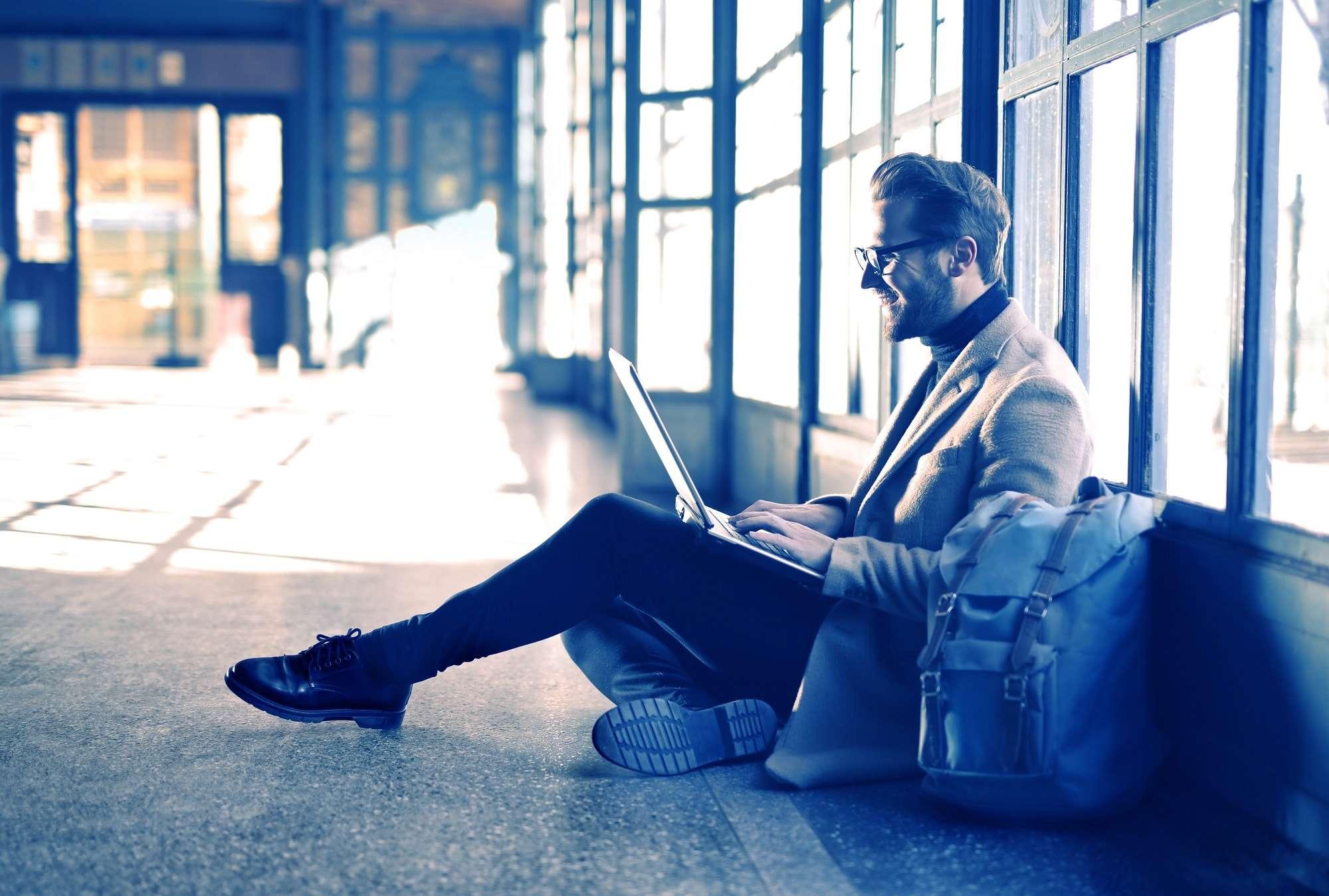 Man op laptop bij vliegveld